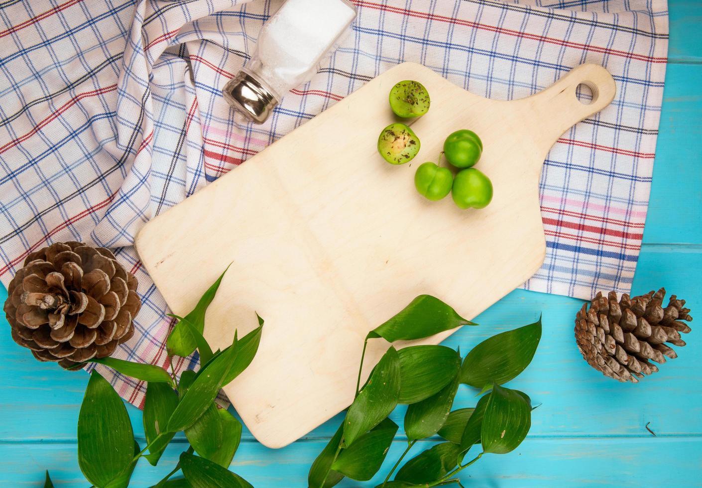 Vue de dessus d'une planche de bois avec des prunes et des pommes de pin sur tissu photo