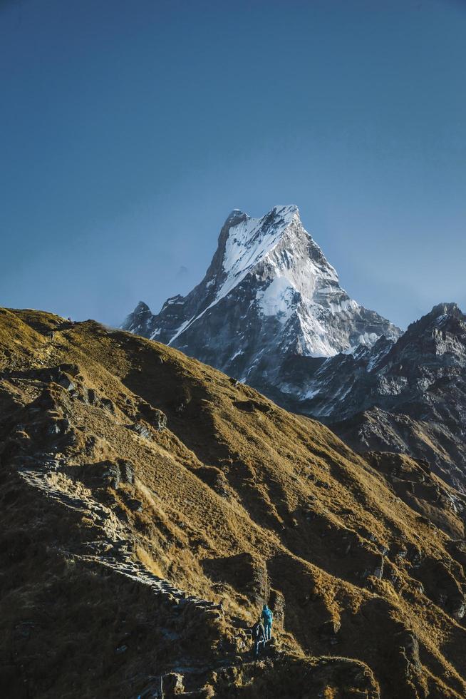 deux personnes au pied d'une montagne photo