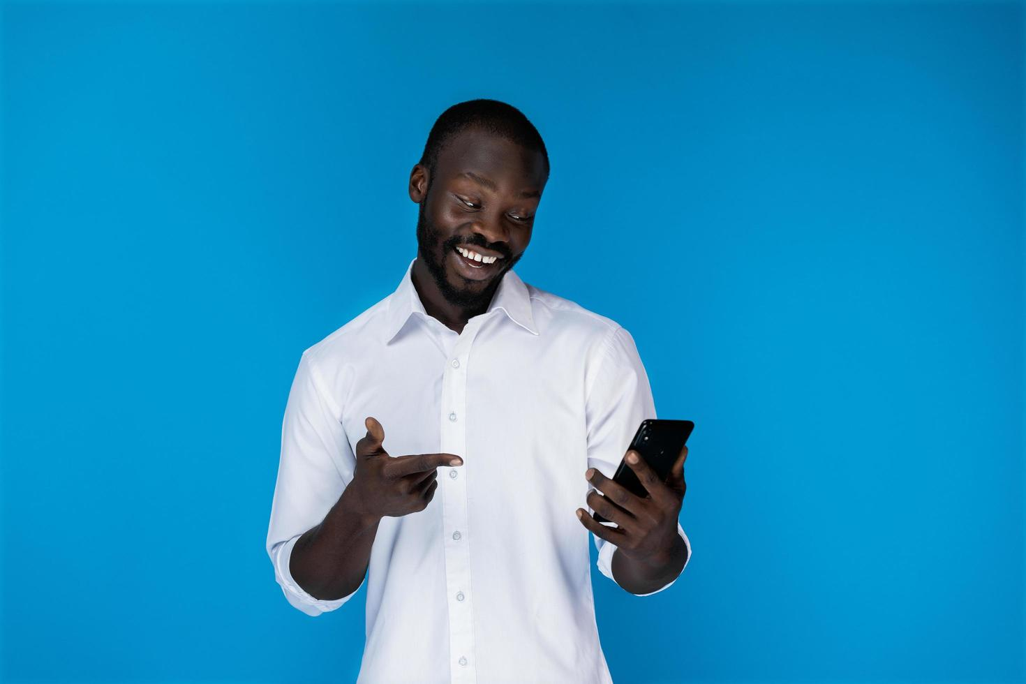 un homme souriant en regardant son téléphone photo