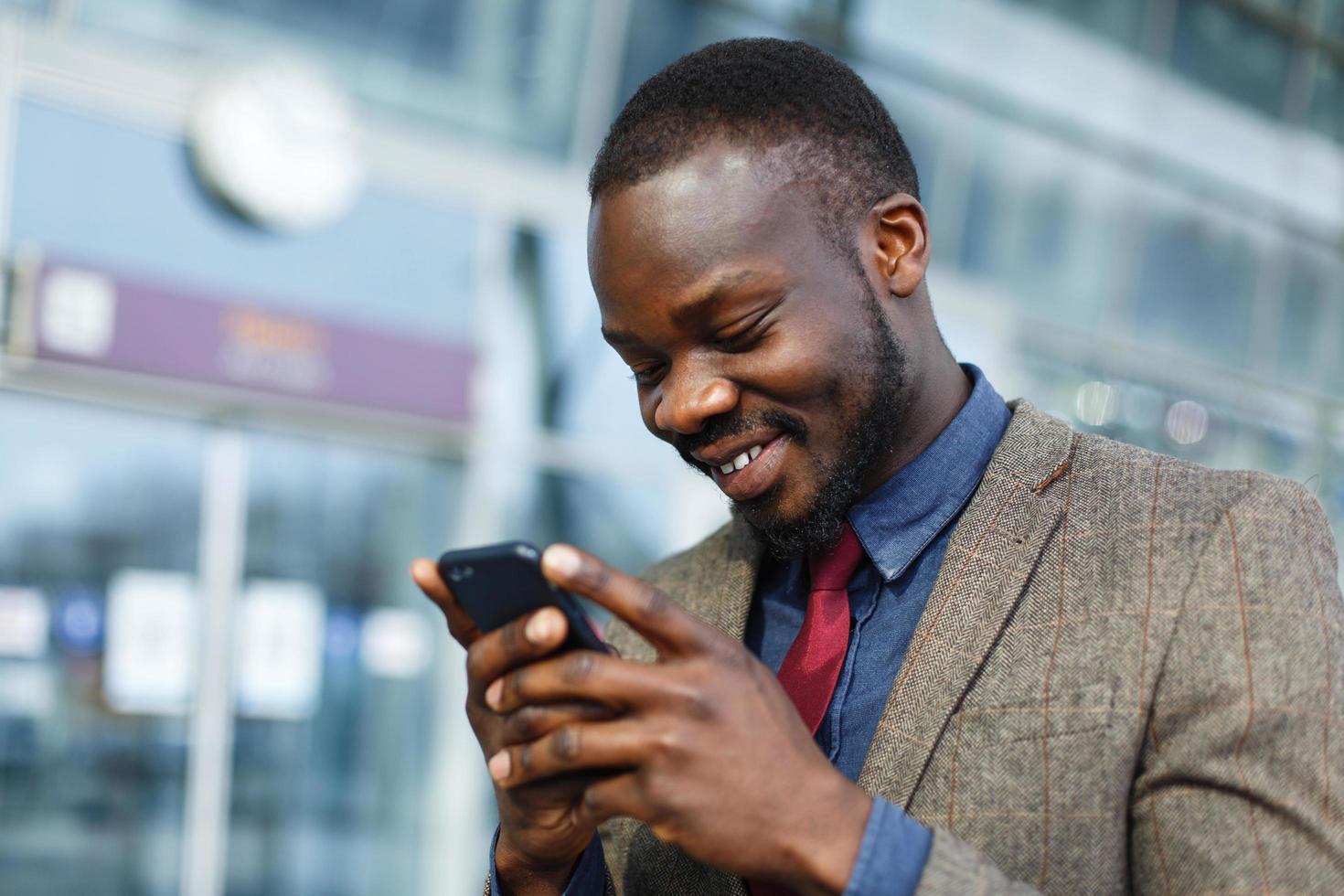 homme souriant tout en envoyant des SMS photo