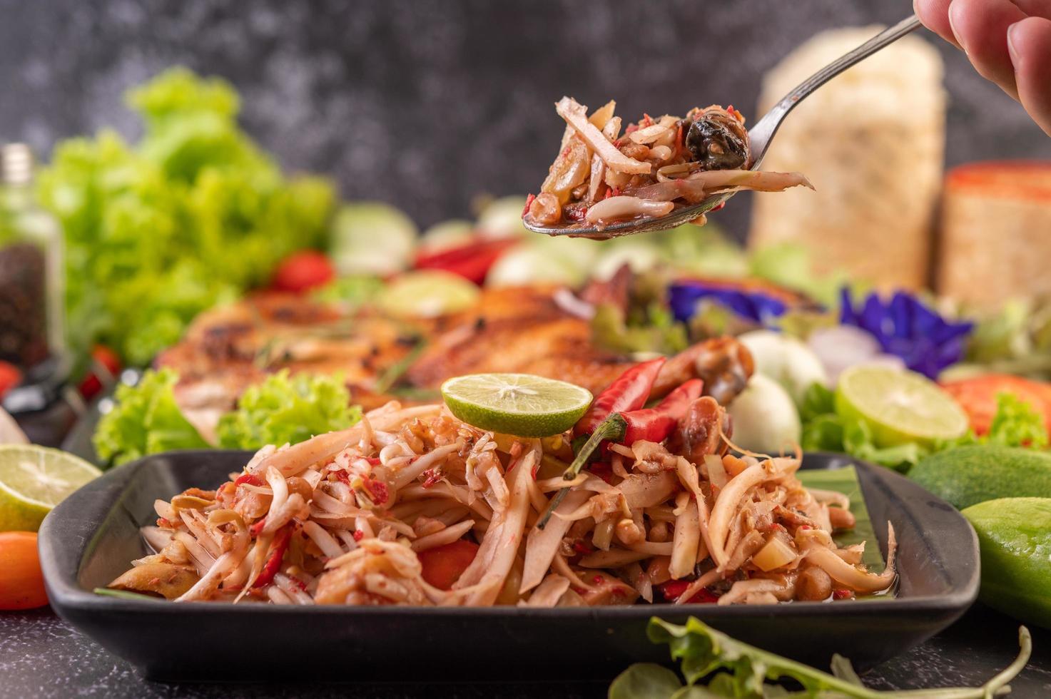 salade de papaye thaï entourée de légumes et de poulet photo