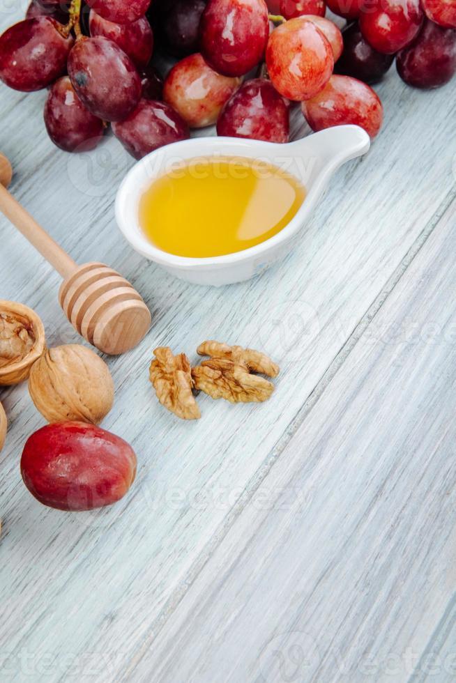 miel avec une cuillère à miel en bois et raisins photo