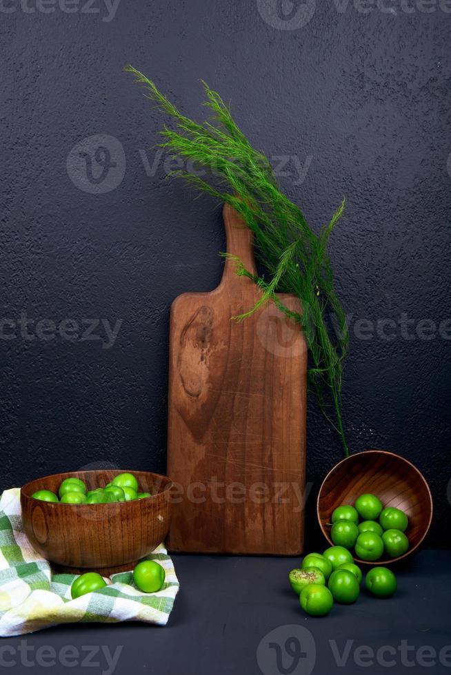 Planche à découper en bois avec fenouil et prunes vertes aigres sur fond noir photo