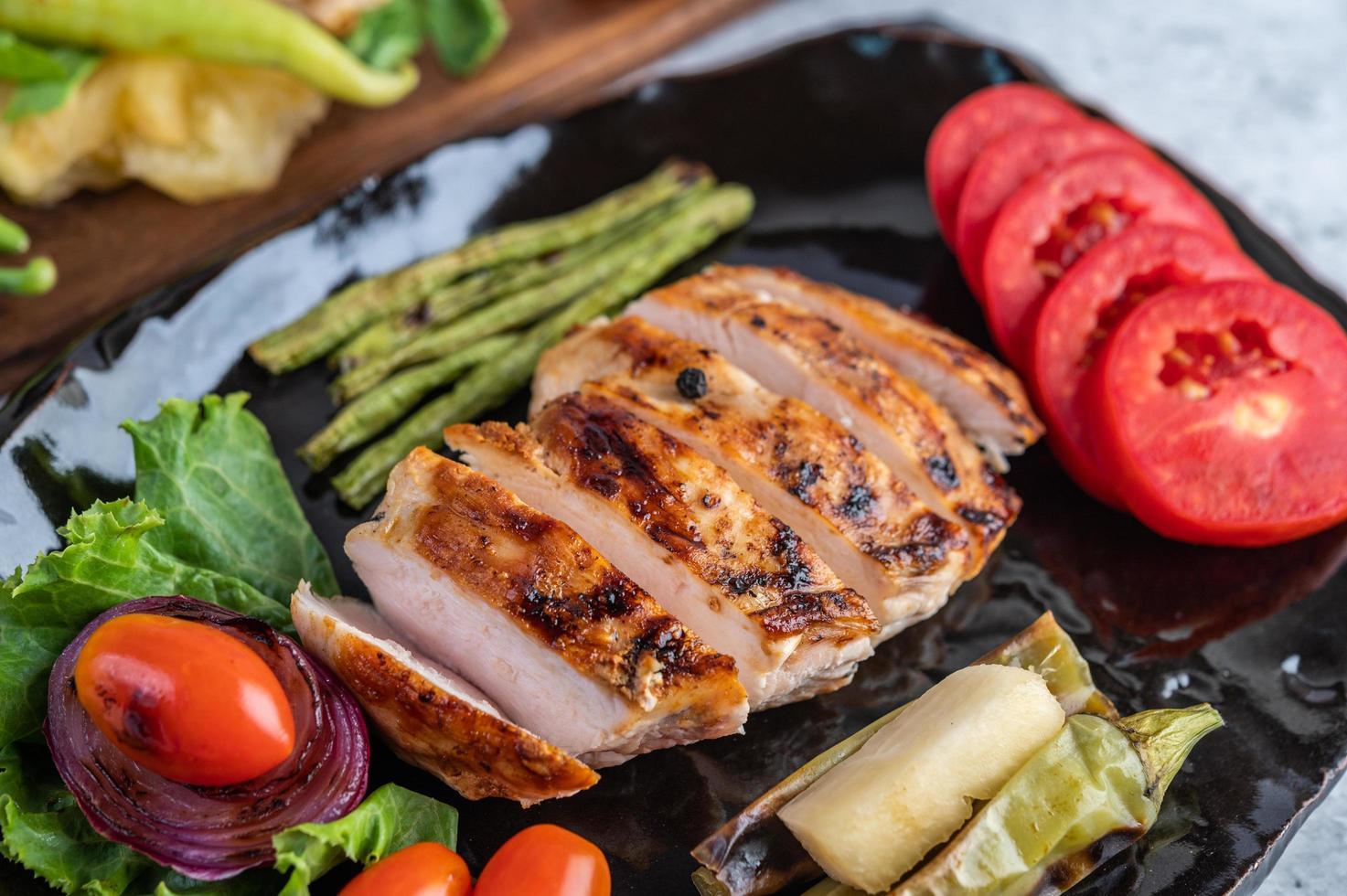 Steak de poulet avec salade de légumes sur une plaque noire photo