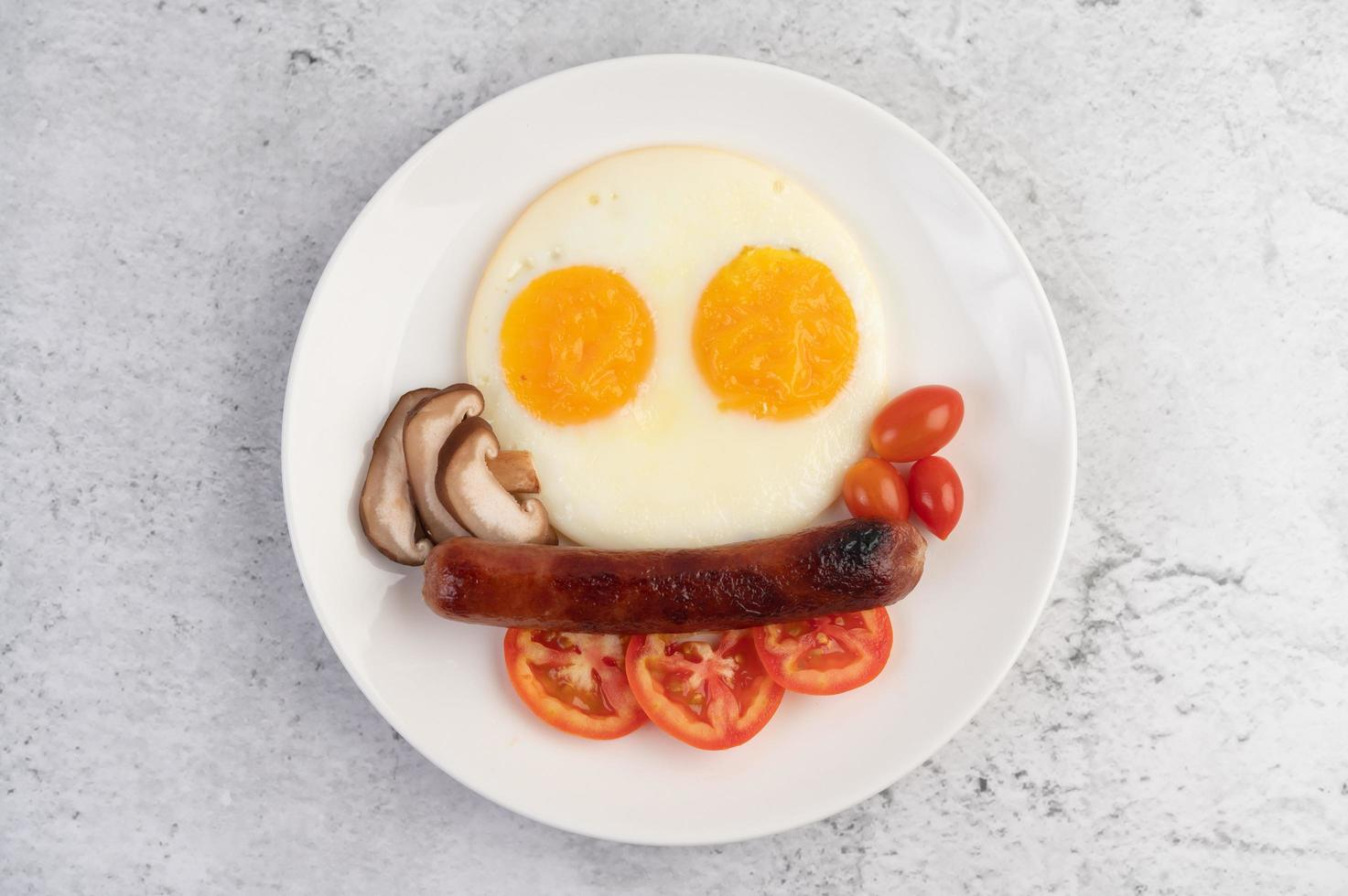 assiette petit-déjeuner avec œufs au plat, tomates, saucisse chinoise et champignons photo