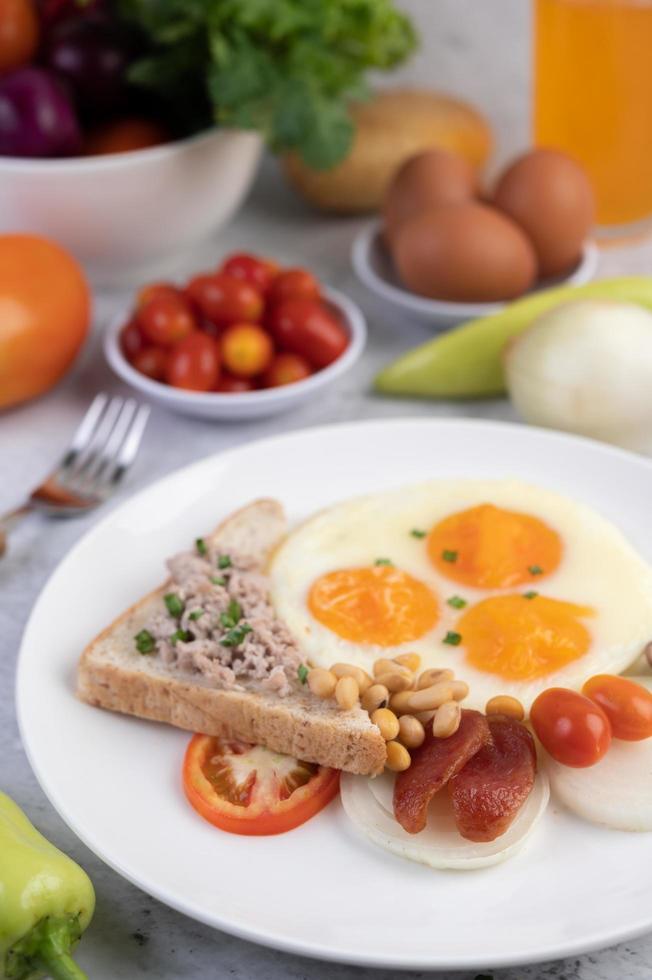 œufs au plat, saucisses, porc haché, pain et haricots rouges photo