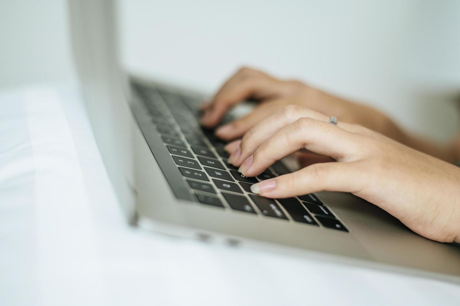 mains de femme tapant sur ordinateur portable photo