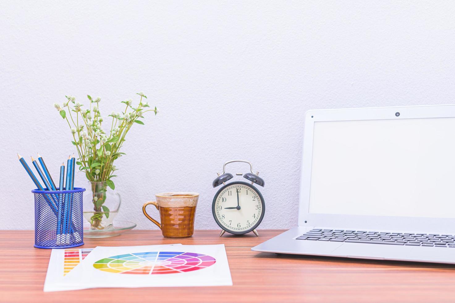 ordinateur portable, documents et fleur sur le bureau photo