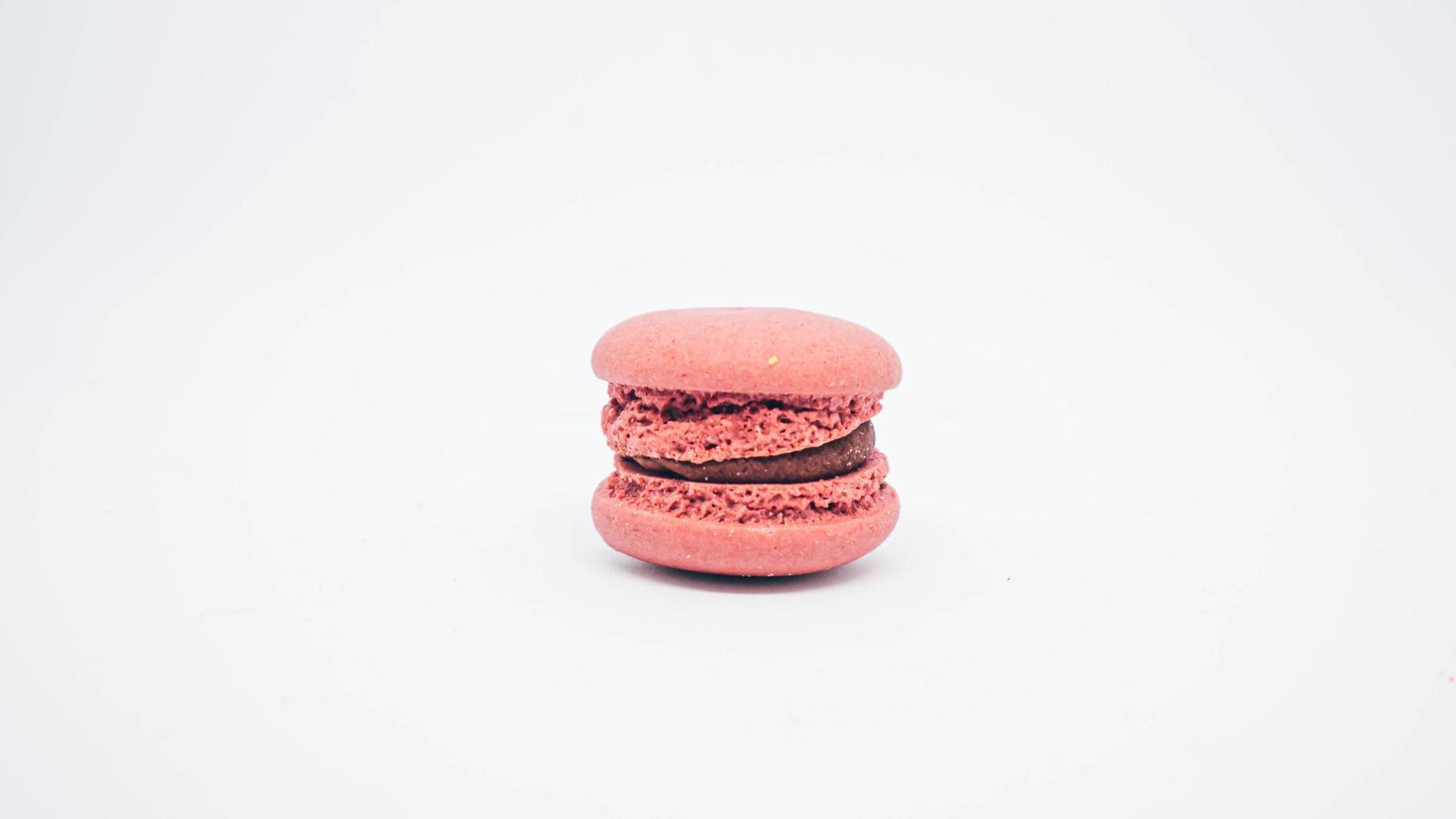 Macaron rose pastel avec crème isoler sur fond blanc photo
