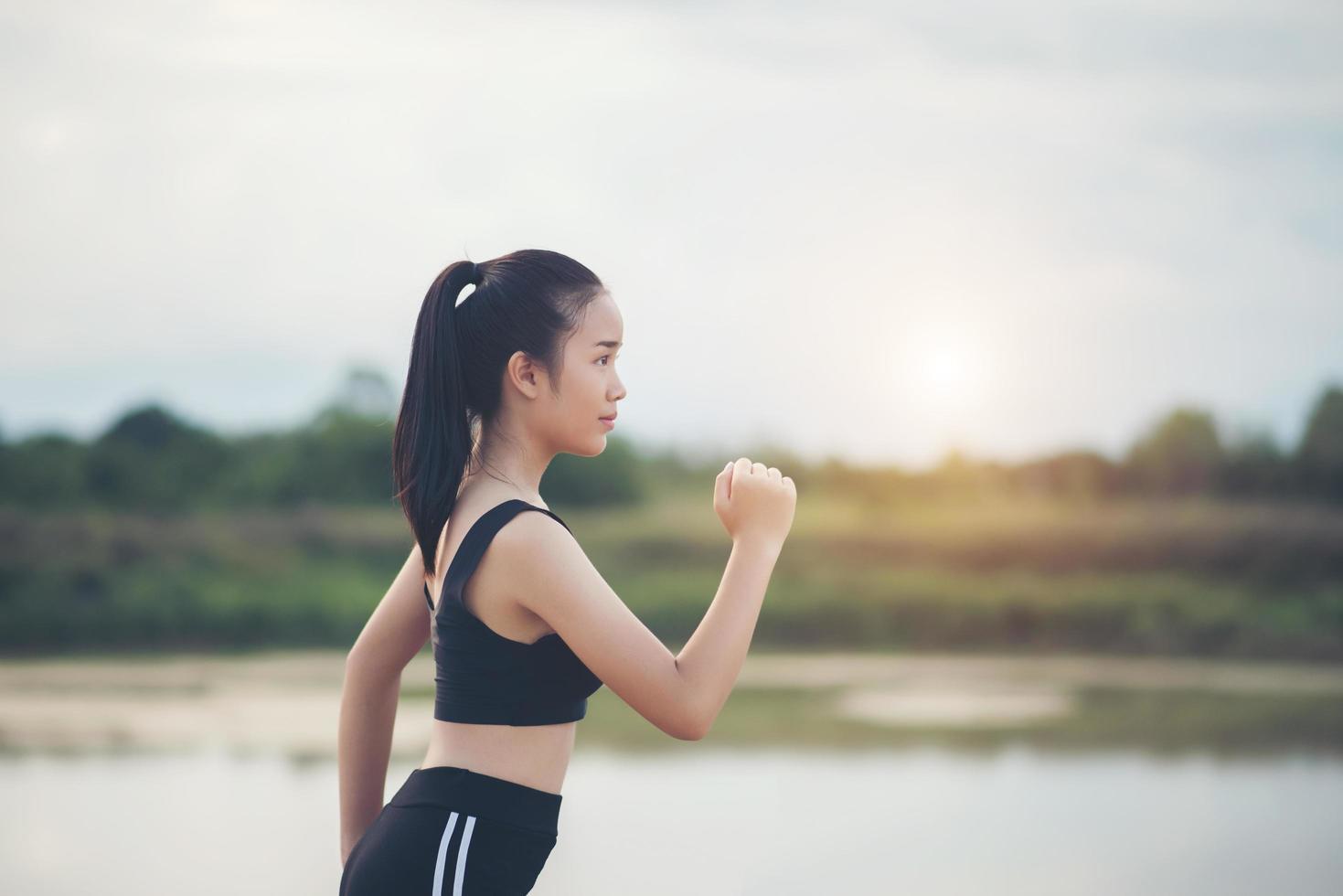 Une jeune coureuse heureuse jogging à l'extérieur photo