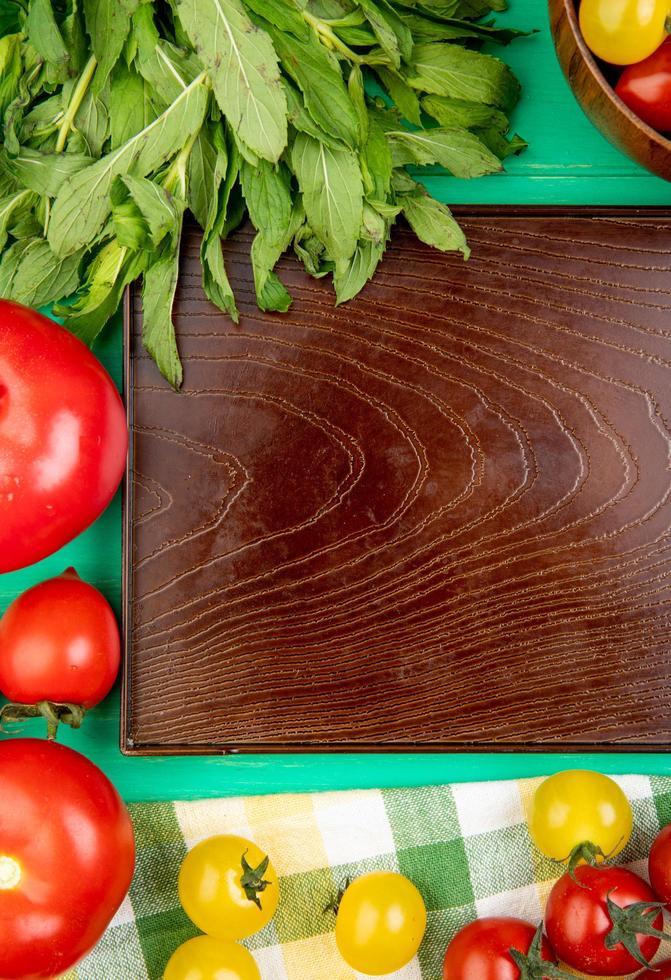 Vue de dessus des légumes comme la menthe verte laisse les tomates autour du plateau vide sur fond vert photo