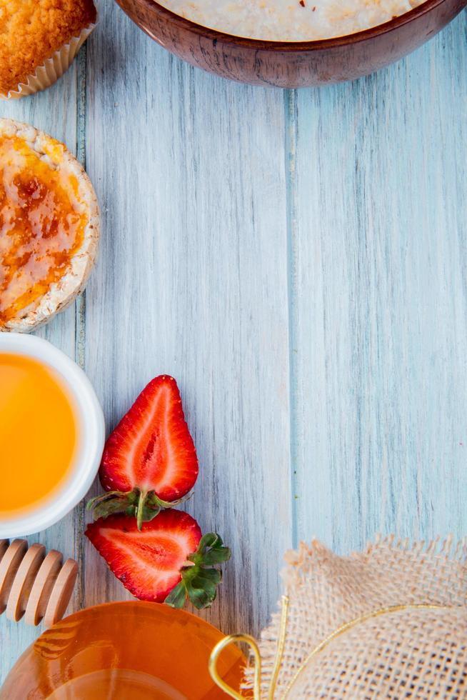 Vue de dessus de la moitié des fraises coupées avec de l'avoine pain croustillant sirop de pêche beurre cupcake sur fond de bois avec copie espace photo