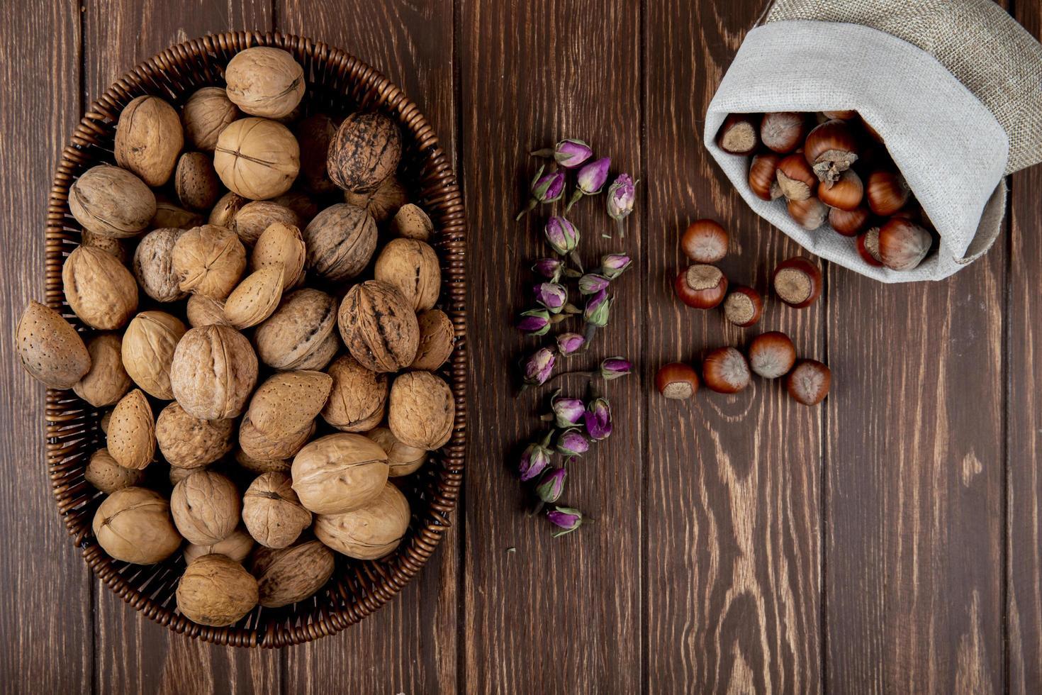 Vue de dessus de noix entières dans un panier en osier et noisettes éparpillées à partir d'un sac sur fond de bois photo