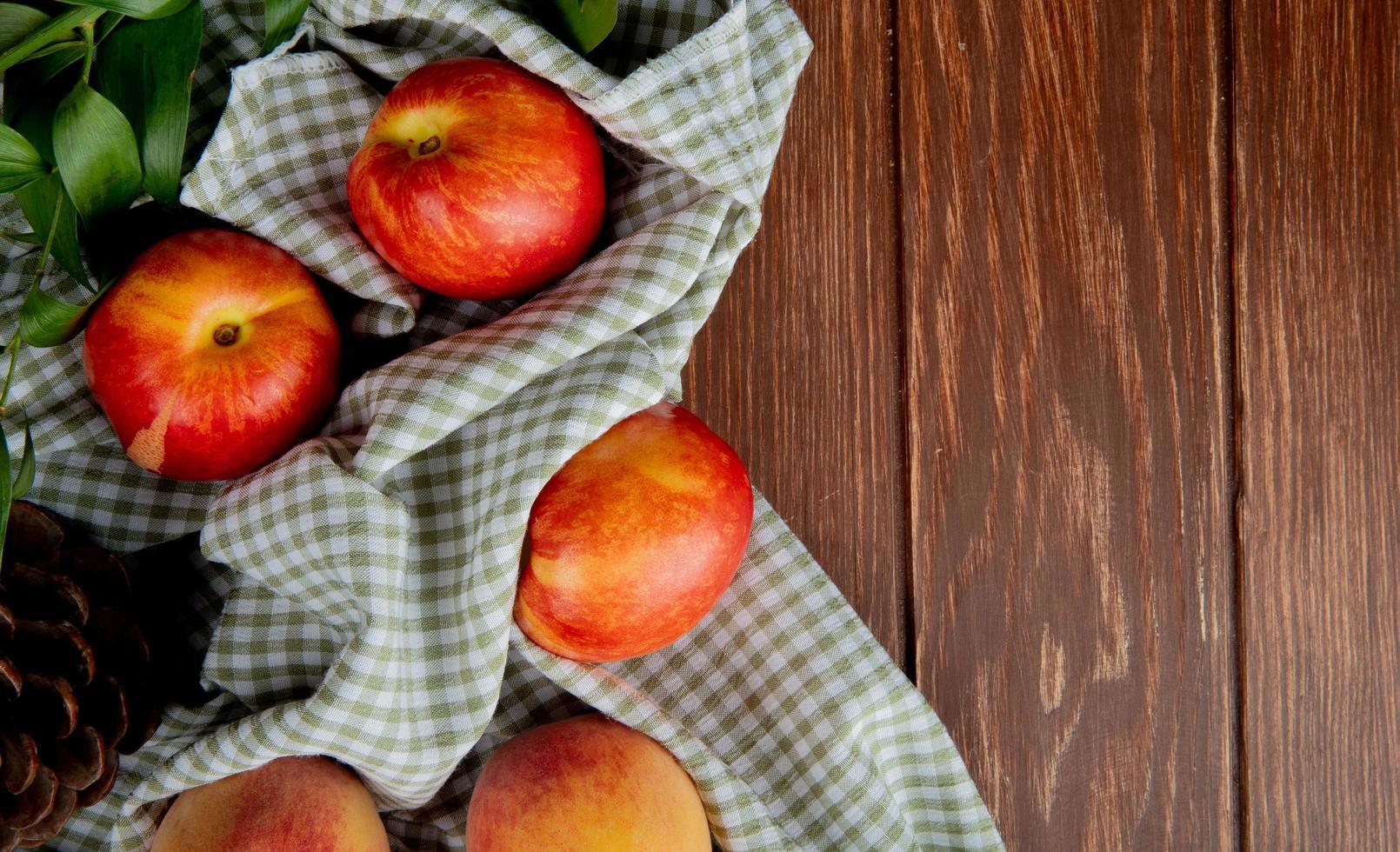 Vue de dessus des pêches et des pommes de pin sur tissu sur le côté gauche et fond en bois avec copie espace photo
