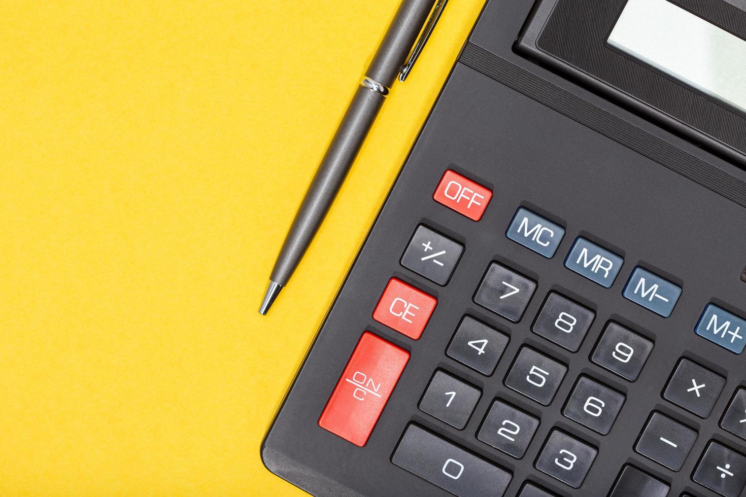 calculatrice et stylo sur fond jaune photo