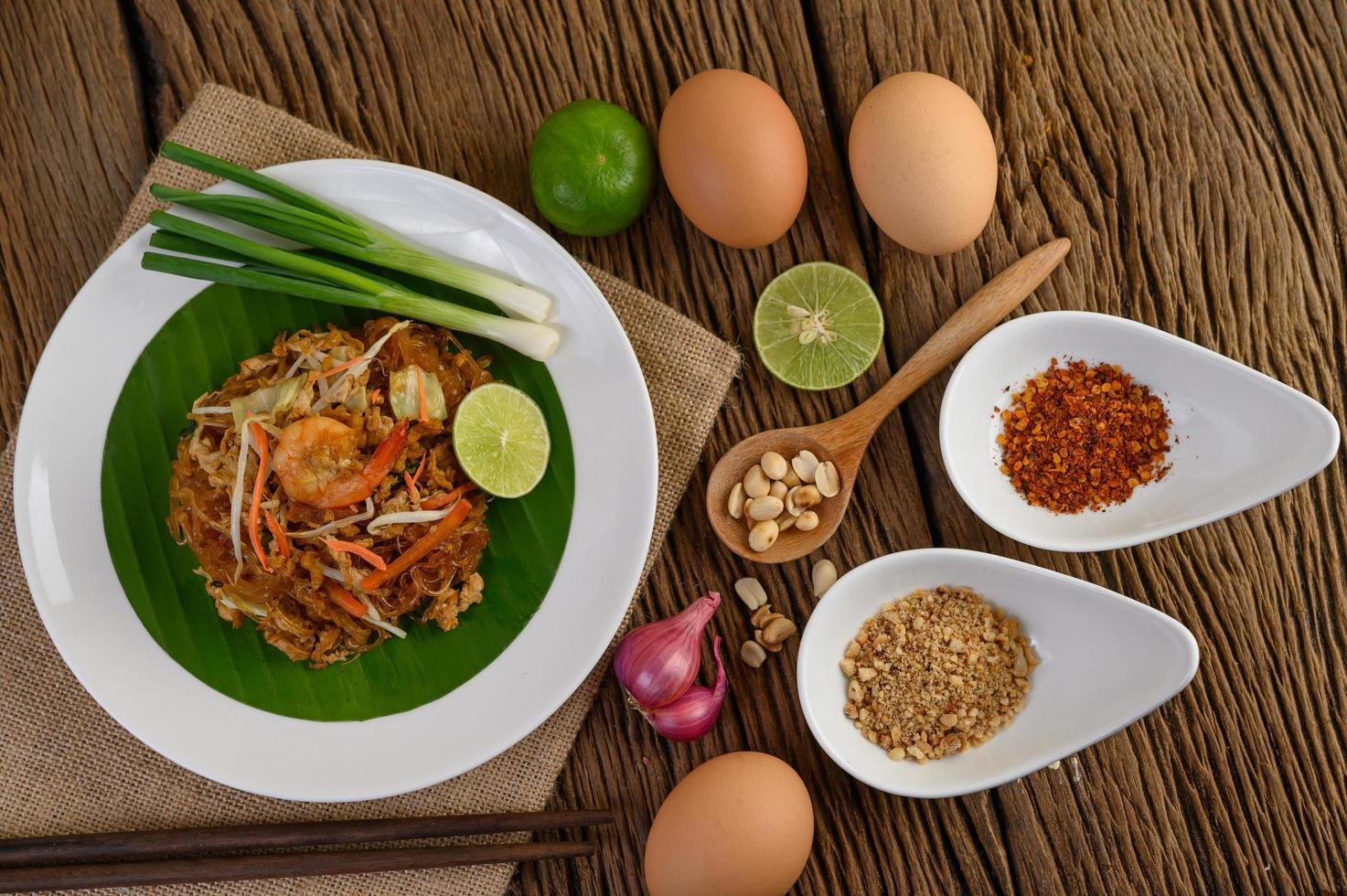 Pad thai crevettes dans un bol avec œufs, oignon nouveau et assaisonnements photo