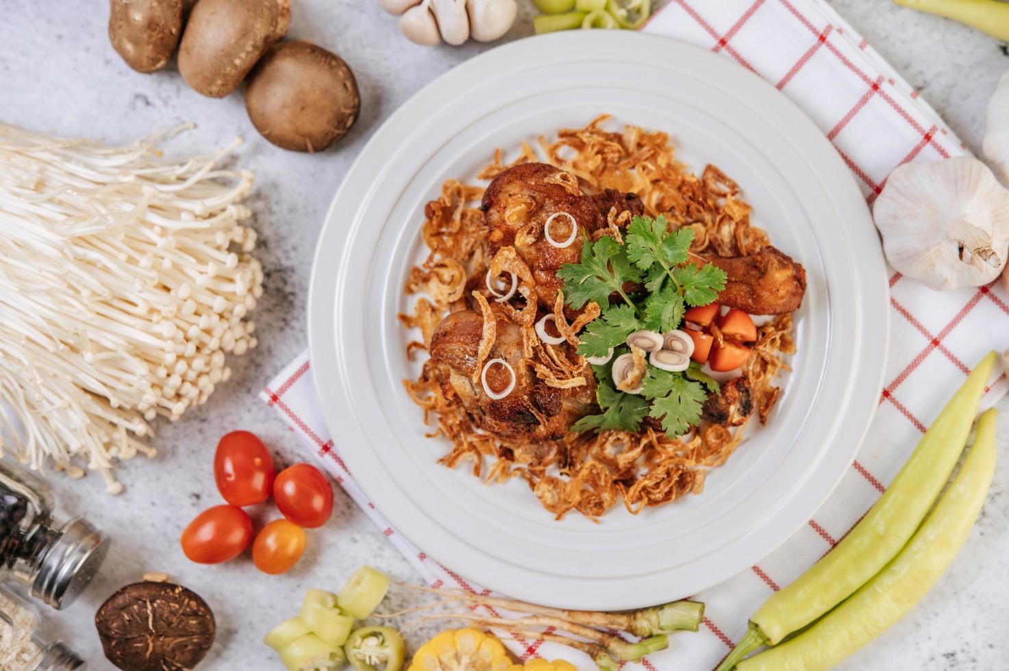 cuisses de poulet frites avec tomate, chili, oignon frit, laitue, maïs et champignon photo