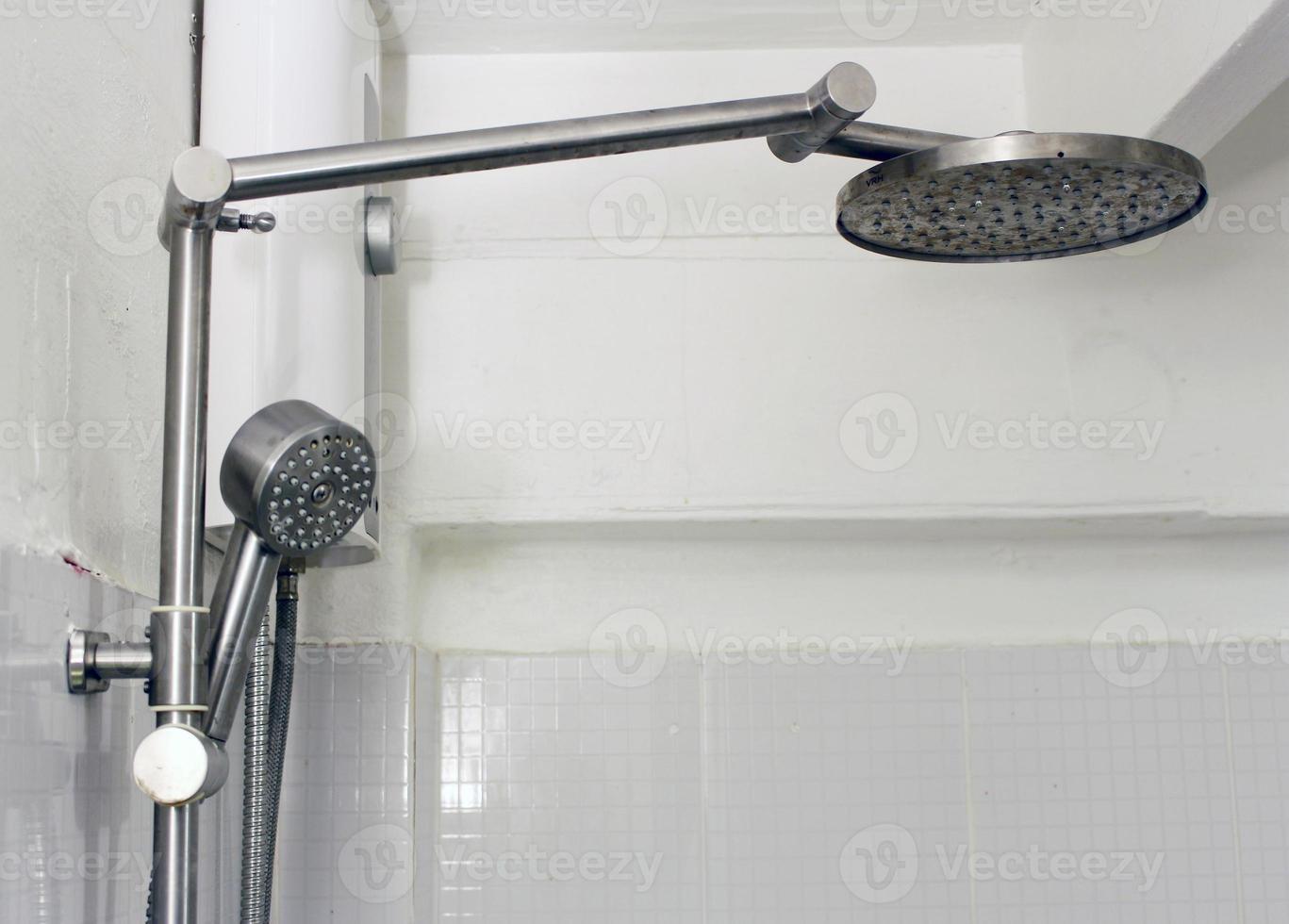 Douche de bain sur mur de carreaux blancs photo