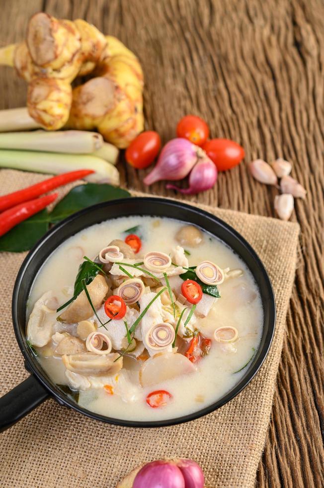 soupe tom kha kai avec feuilles de lime kaffir, citronnelle, oignon rouge, galanga et piment photo