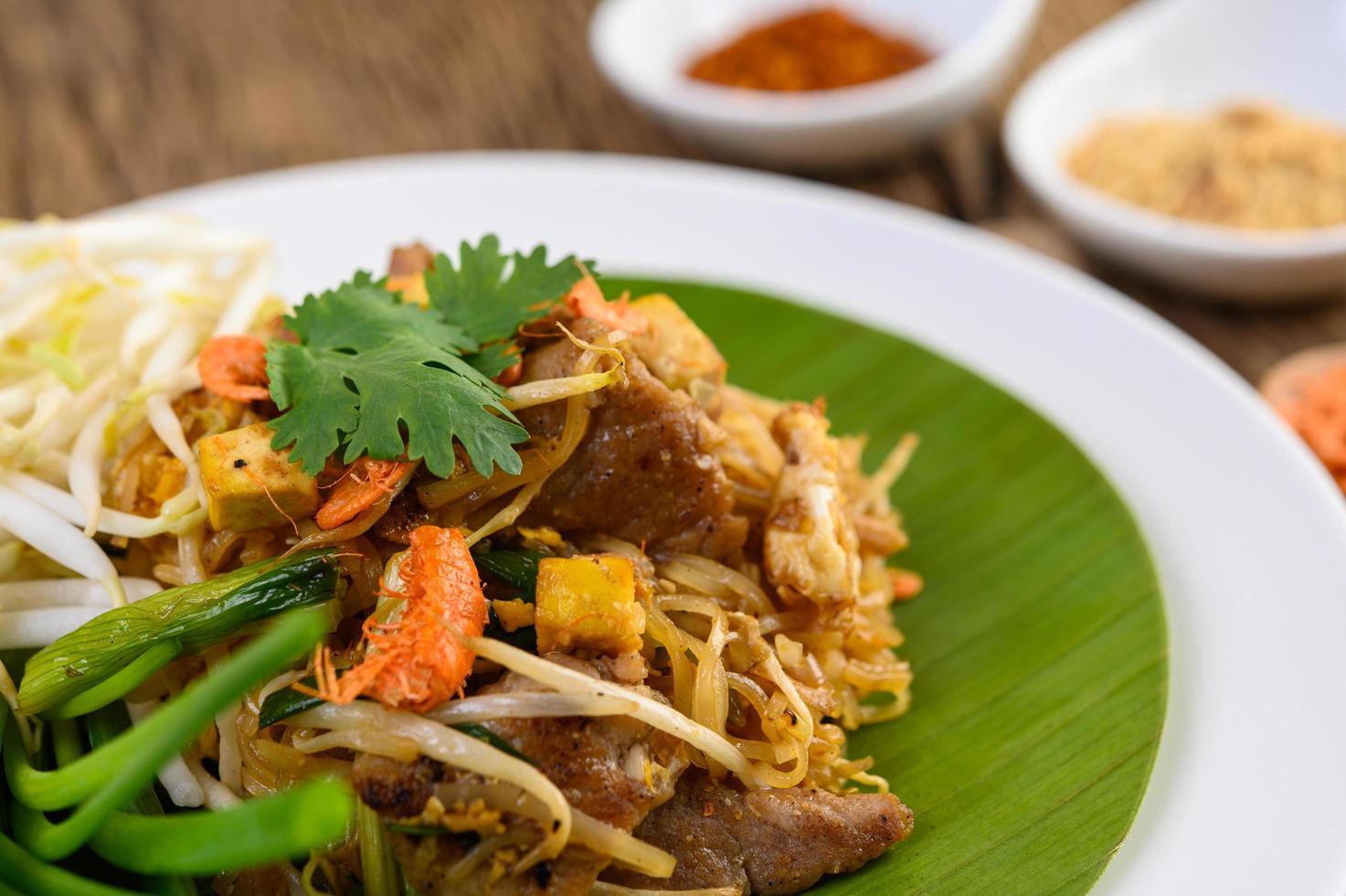 Pad thaï au citron, oeufs et assaisonnement sur une table en bois photo