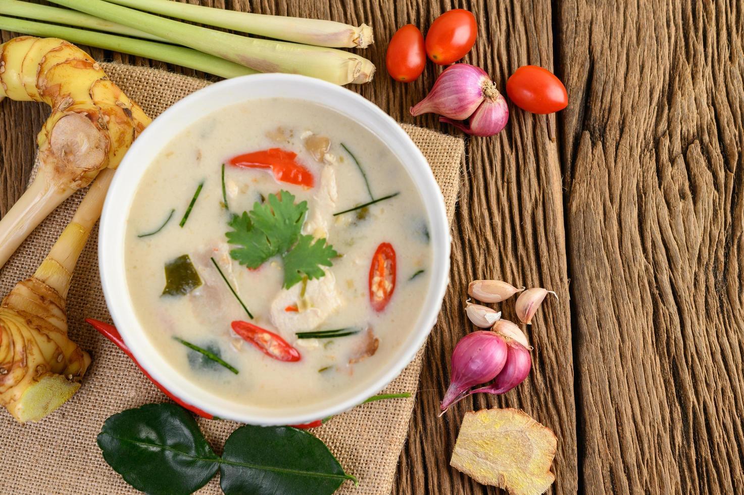Tom kha kai, soupe de noix de coco thaï sur planche de cuisine en bois photo