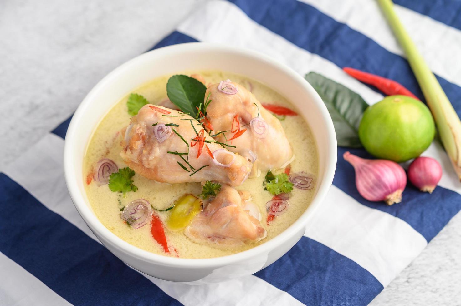Tom kha kai, soupe de noix de coco thaï sur un chiffon bleu photo