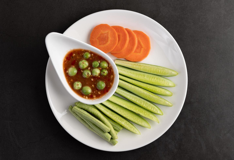 sauce à la pâte de crevettes dans un bol avec concombre, haricots verts et carottes photo