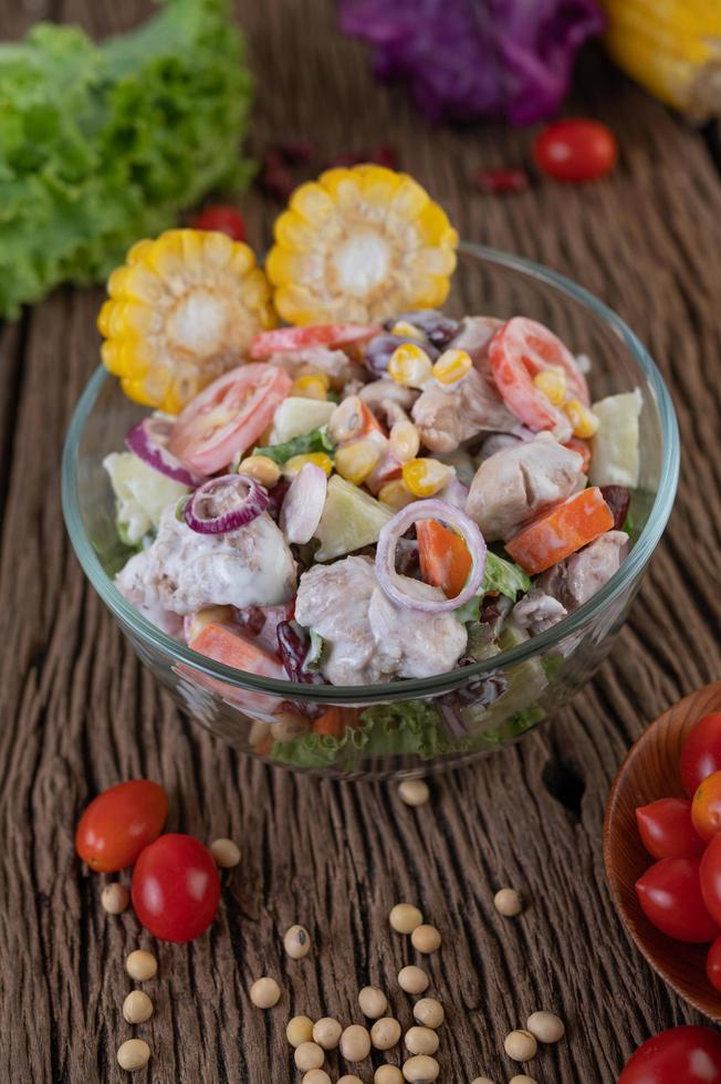 Salade de fruits et légumes dans un bol en verre sur table en bois photo