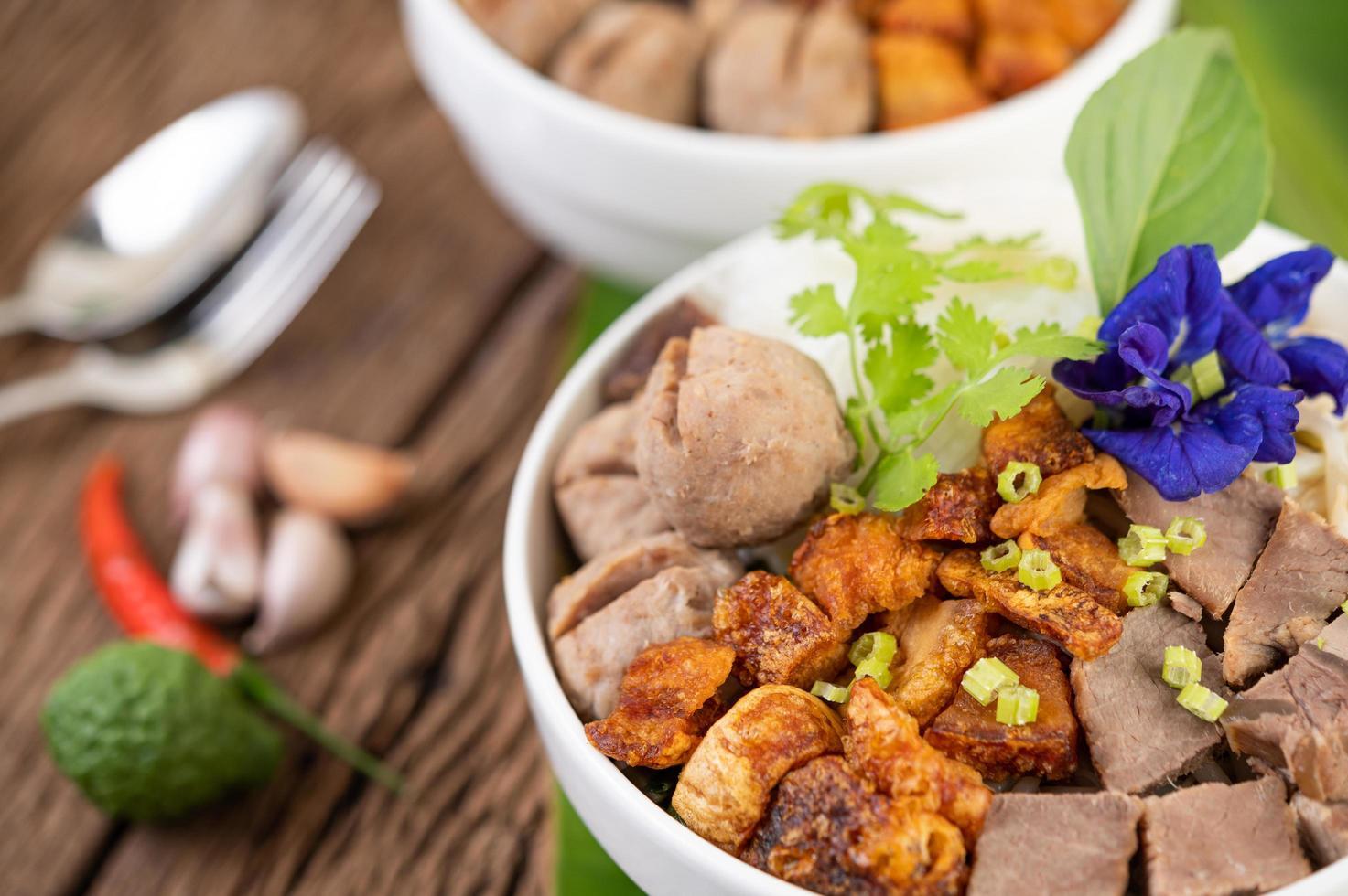 nouilles dans un bol avec du porc croustillant et des boulettes de viande photo