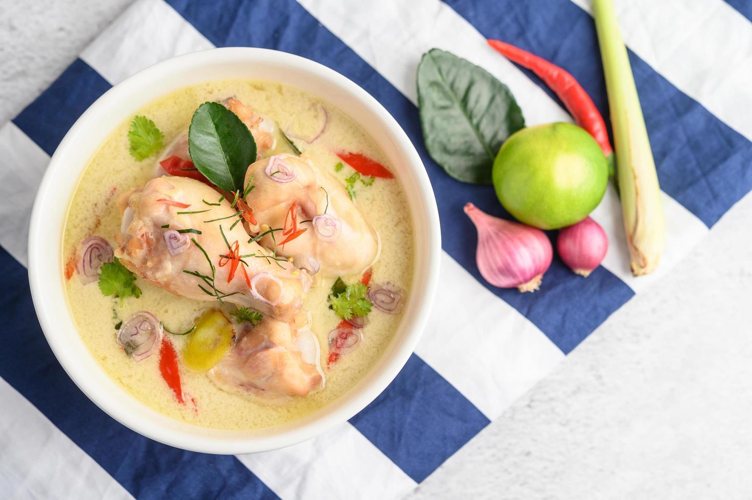 Tom kha kai, soupe thaï à la noix de coco sur un chiffon à rayures bleues photo