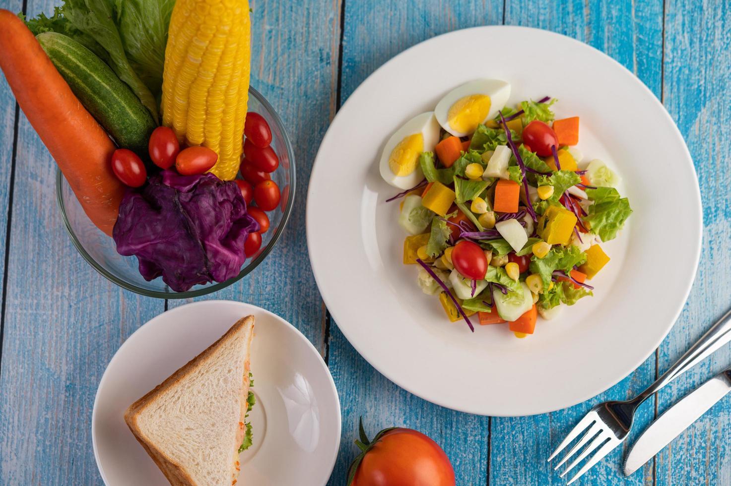 salade fraîche sur une assiette blanche avec un sandwich et des tomates photo