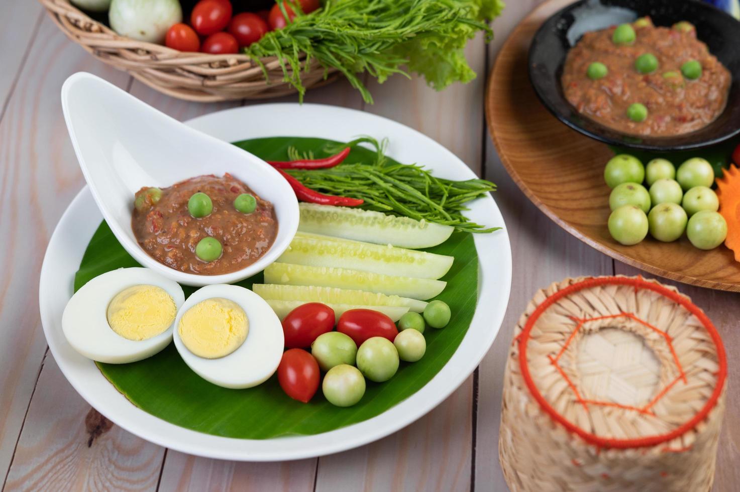 pâte de pâte de piment dans un bol avec aubergines, carottes, chili et concombres dans un panier photo