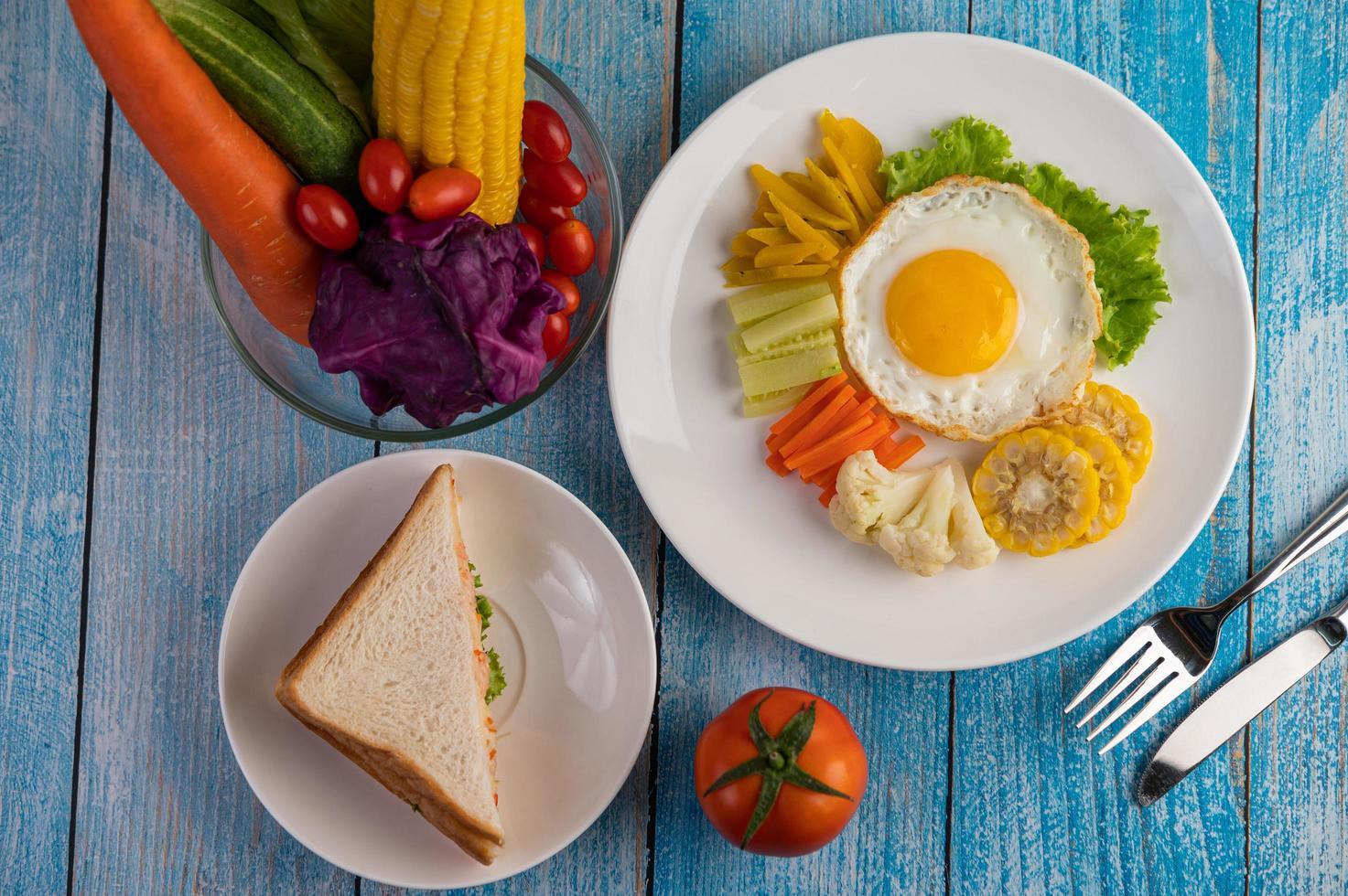 petit-déjeuner aux œufs frits avec œuf, salade, citrouille, concombre, carotte et maïs photo