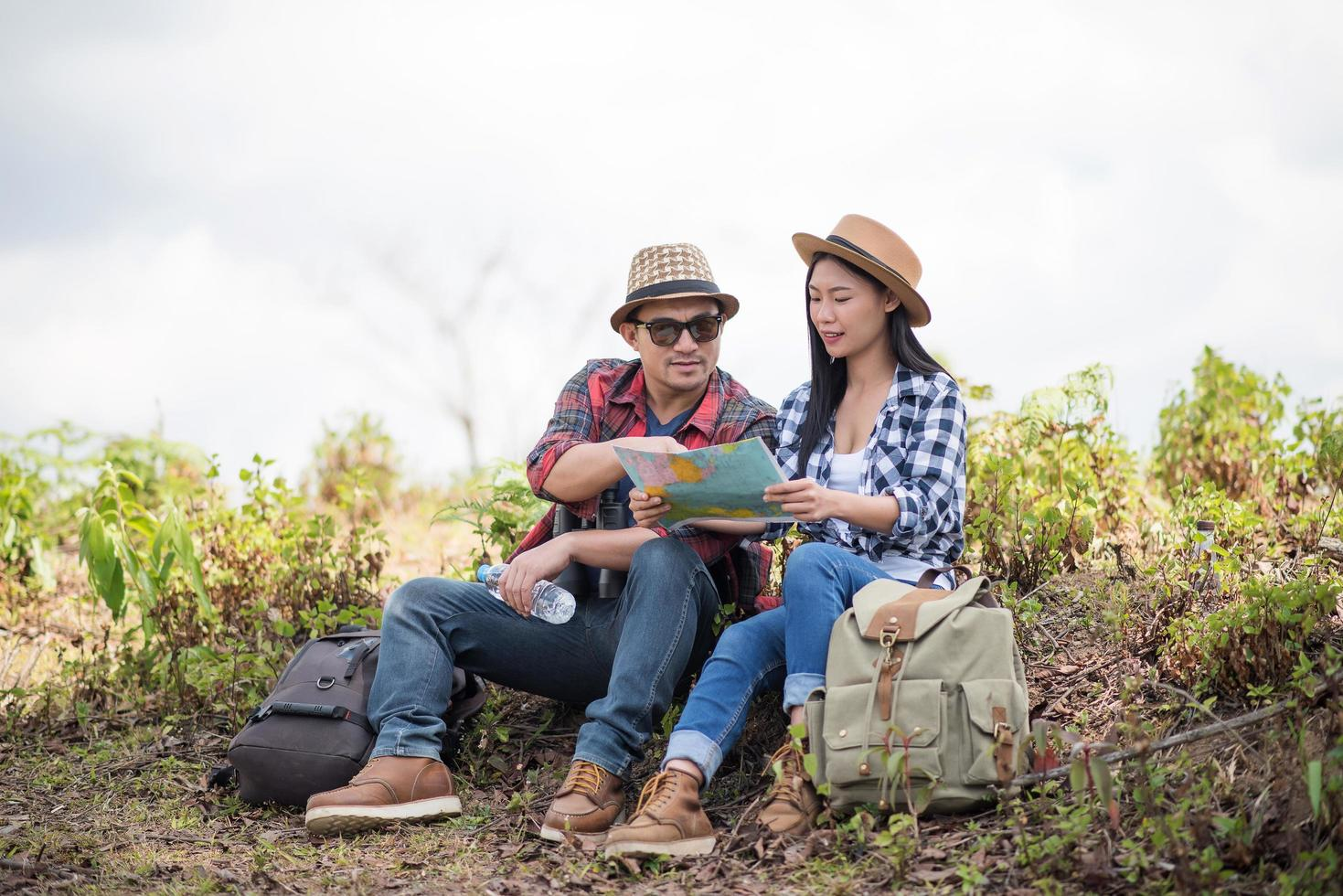 jeune couple regardant la carte lors d'une randonnée dans la forêt photo