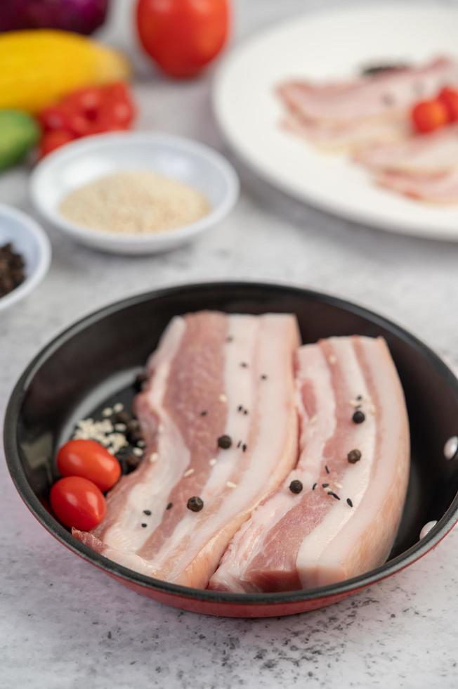 poitrine de porc dans une casserole avec graines de poivron, tomates et épices photo
