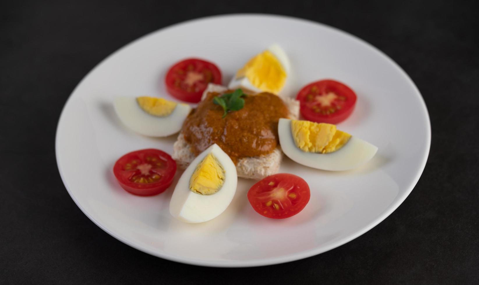 pain garni de pâte de piment avec œufs durs et tomates photo