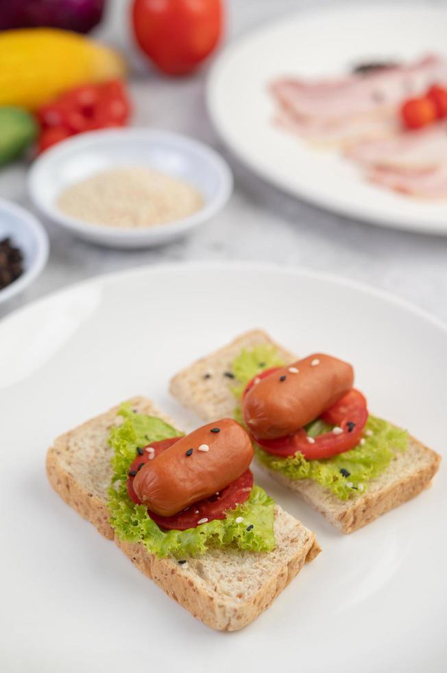 saucisse aux tomates et salade sur pain photo