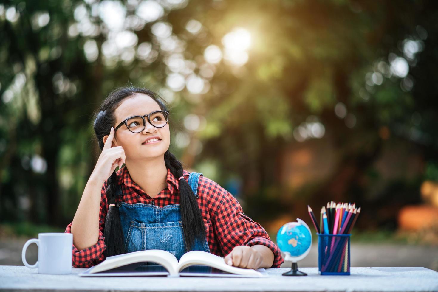 jeune fille lisant et pensant à l'extérieur photo