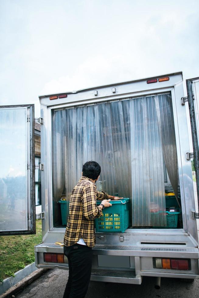 Portrait d'un agriculteur hipster tenant une boîte de fruits pour la vente sur le marché photo