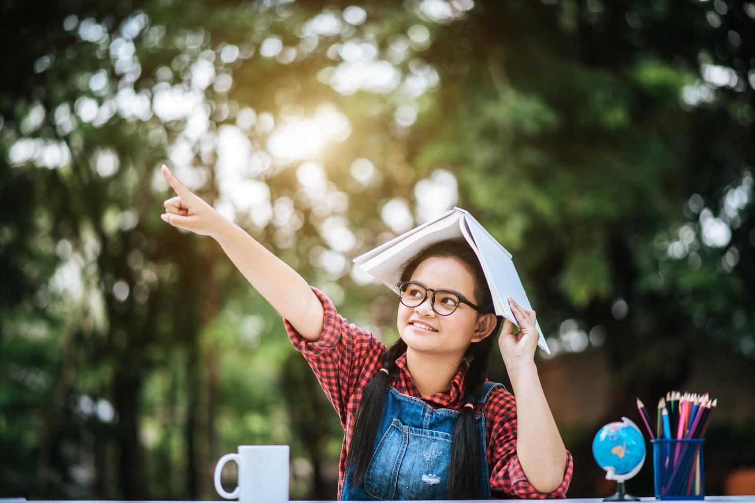 jeune fille avec un livre sur sa tête dans le parc photo