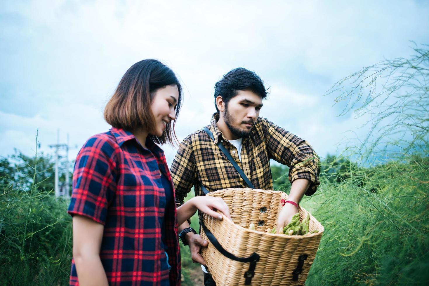 Couple de jeunes agriculteurs récoltant des asperges fraîches photo