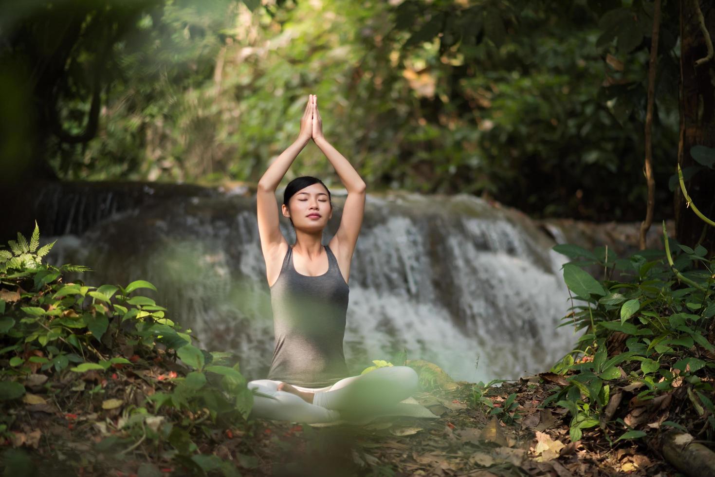 jeune femme, dans, a, pose yoga, séance, près, a, cascade photo