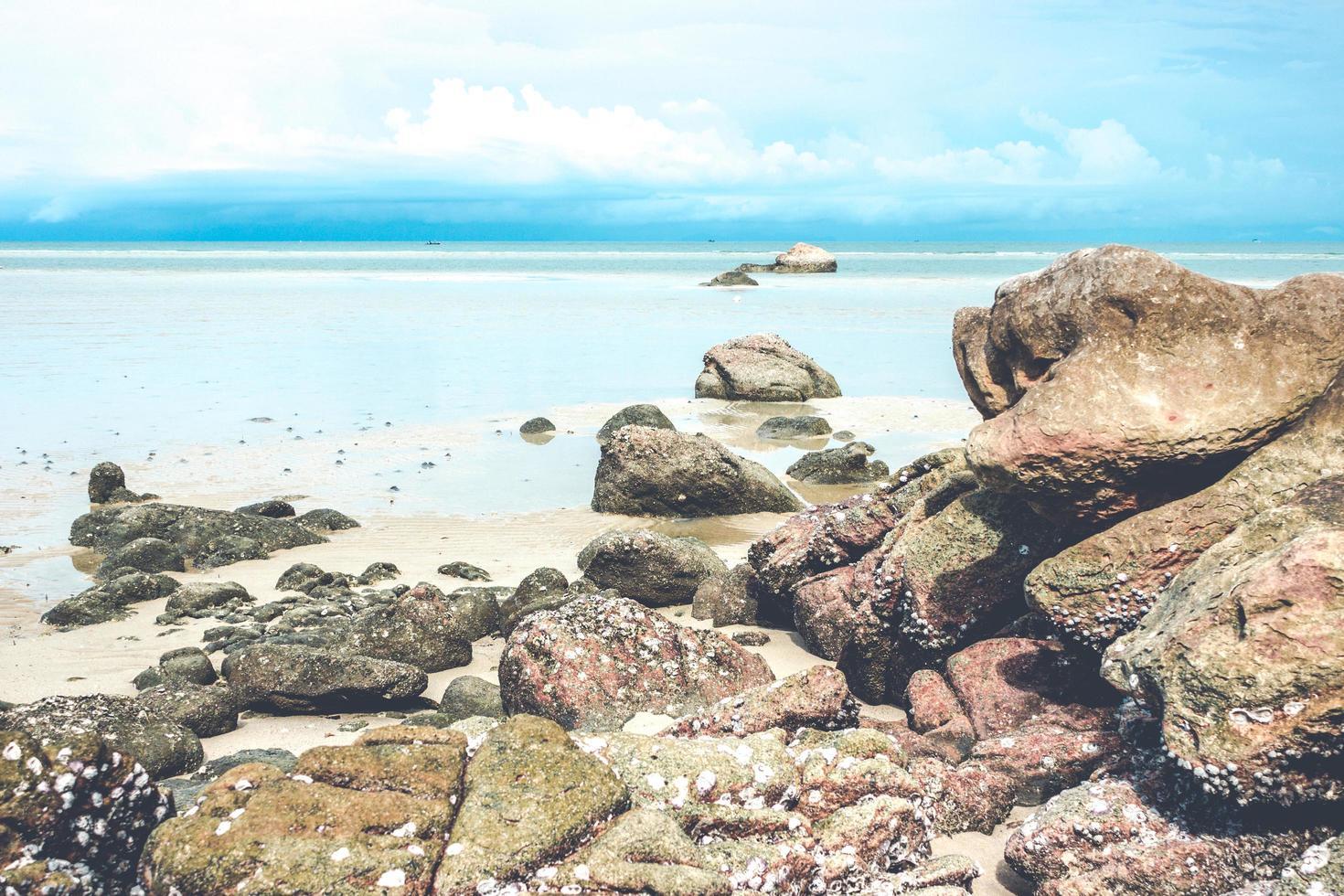 rochers sur la plage avec ciel bleu nuageux photo