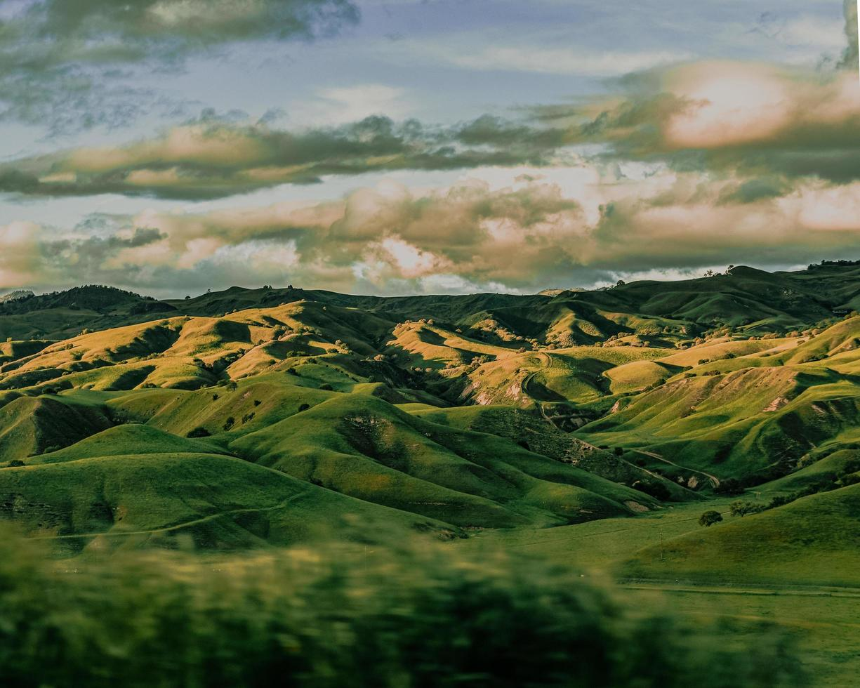 montagnes vertes sous les nuages blancs pendant la journée photo
