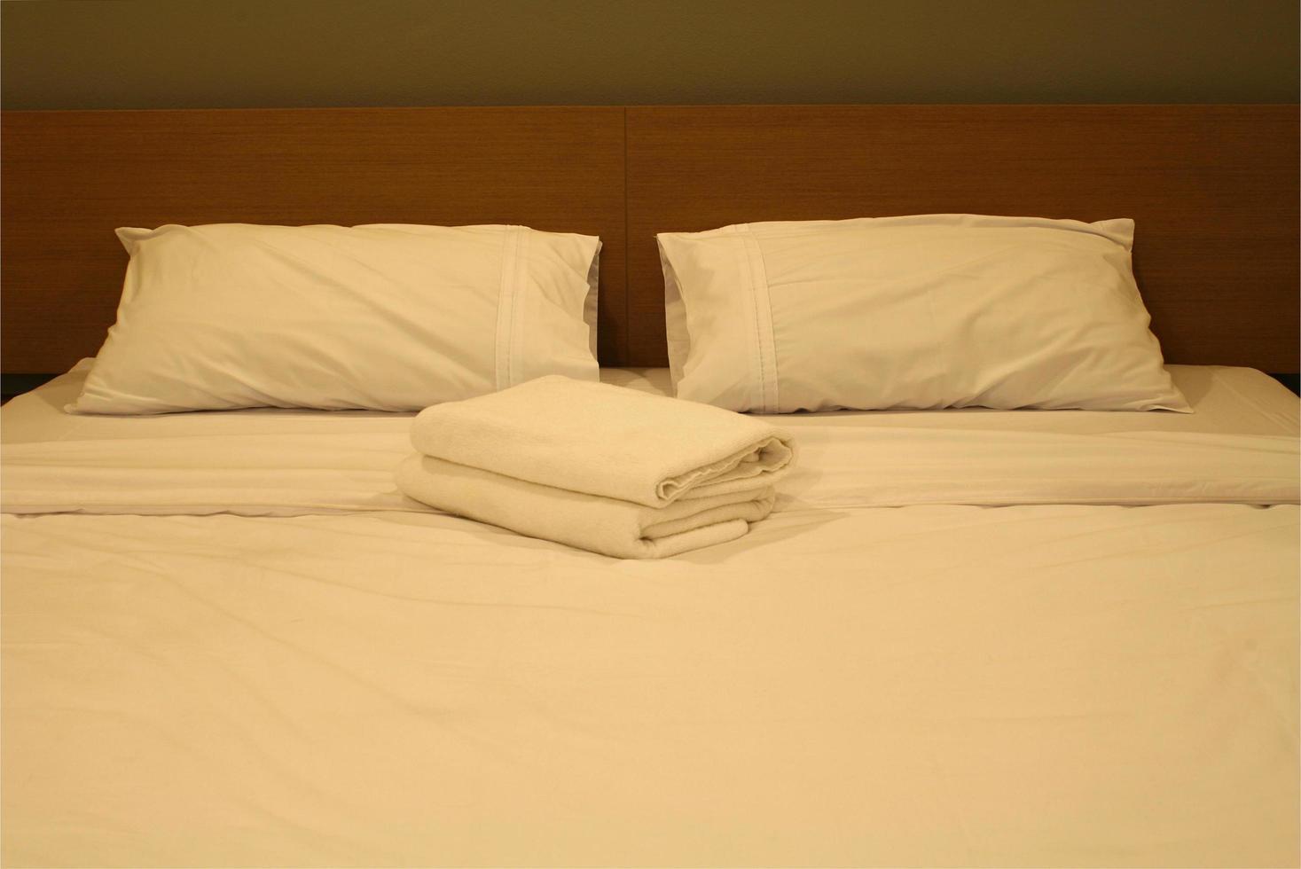 lit d'hôtel avec des draps blancs photo