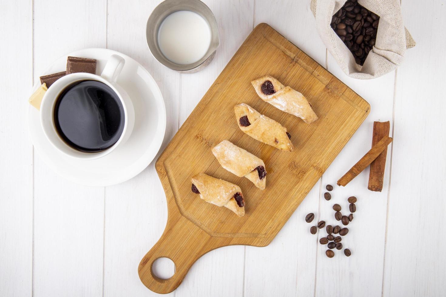 Vue de dessus des biscuits à la farine avec de la confiture de fraises sur une planche de bois avec une tasse de café sur fond blanc photo