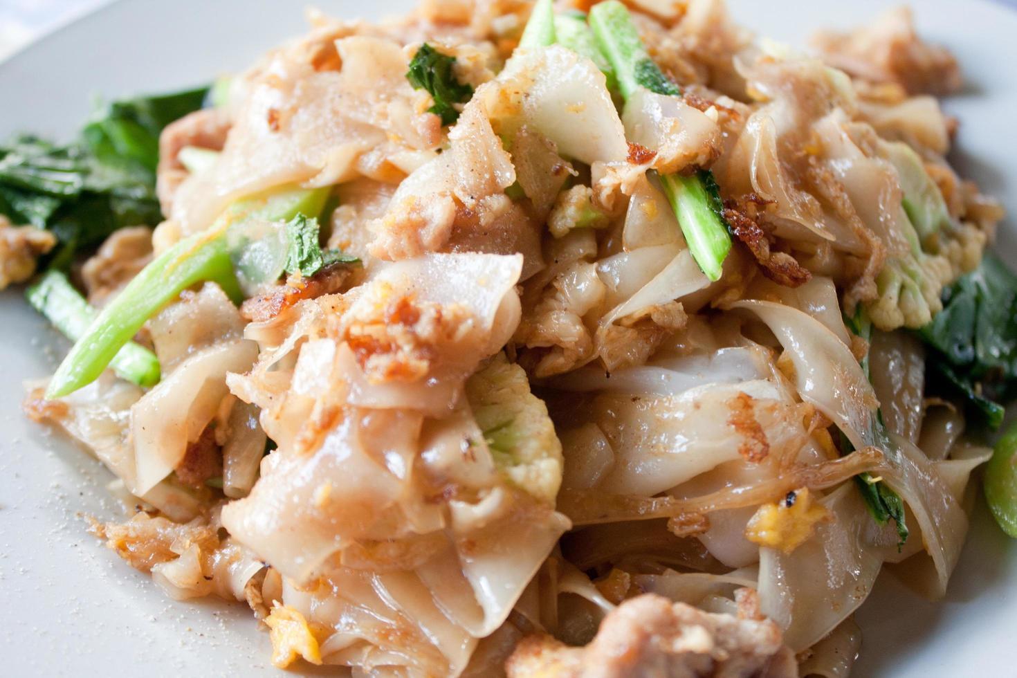 nouilles sautées à la thaï dans une sauce soja avec le porc photo