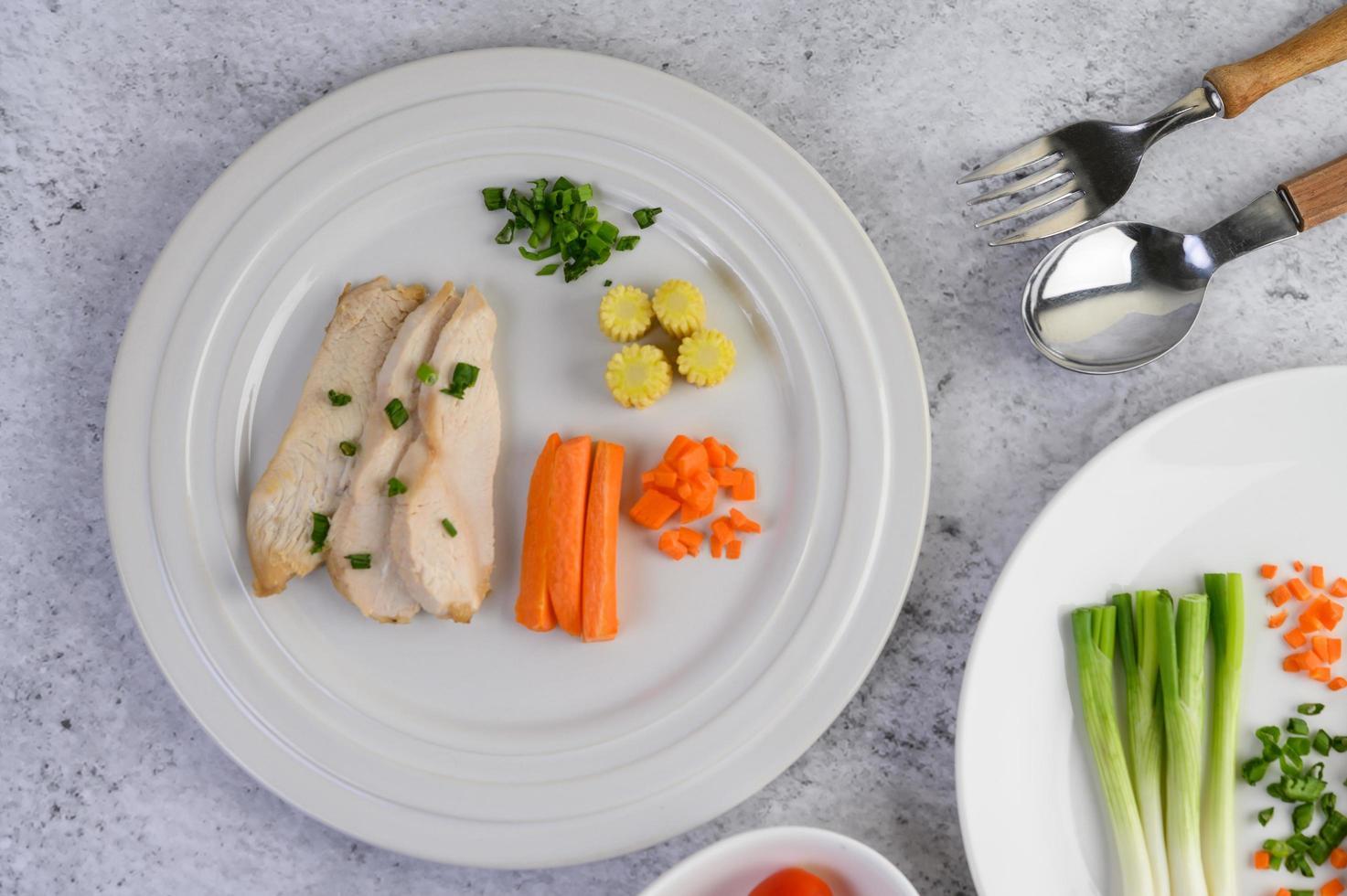 poitrine de poulet cuite à la vapeur sur une assiette blanche avec oignons de printemps et carottes photo