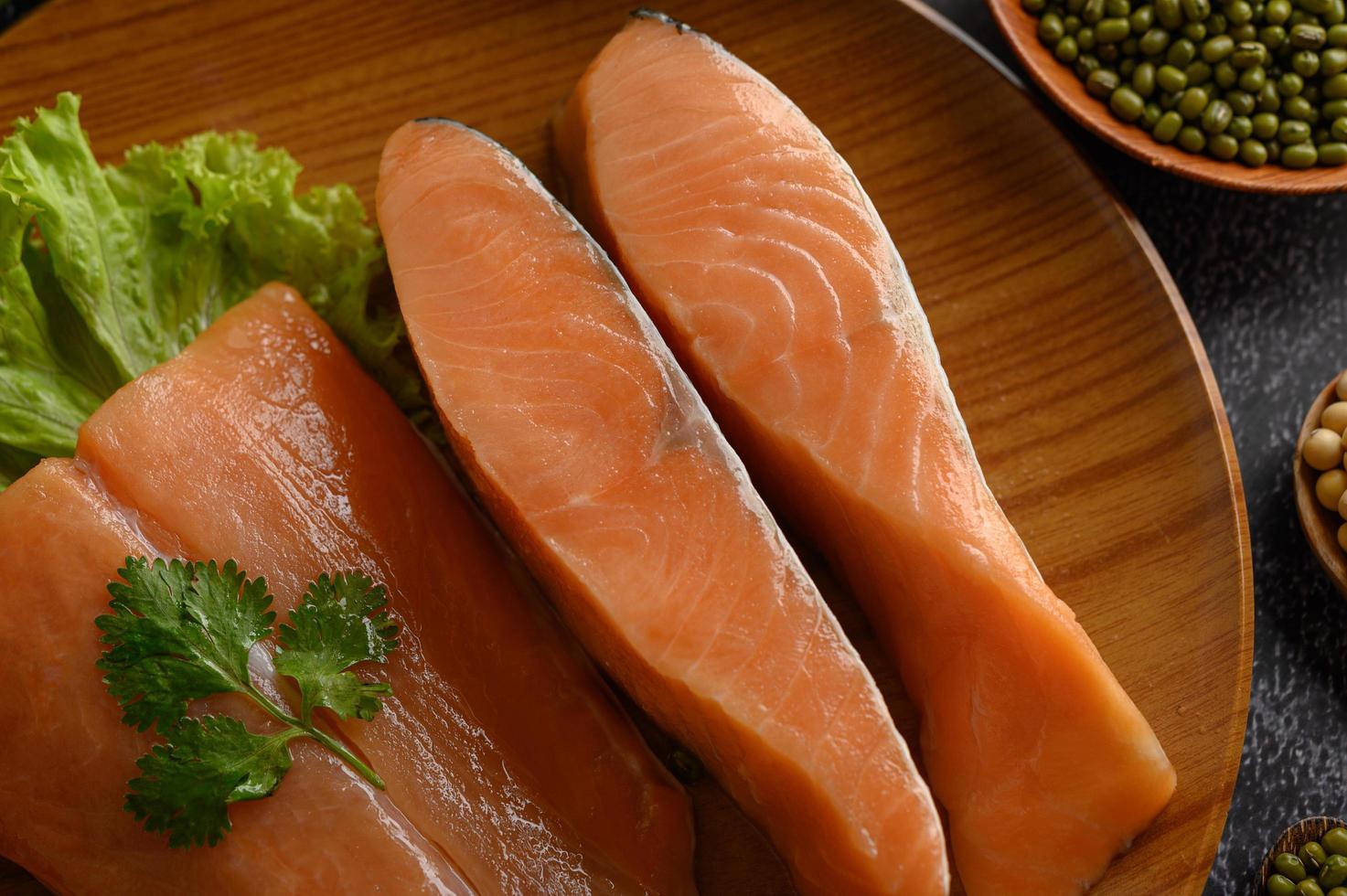 Morceaux de saumon sur une assiette en bois photo