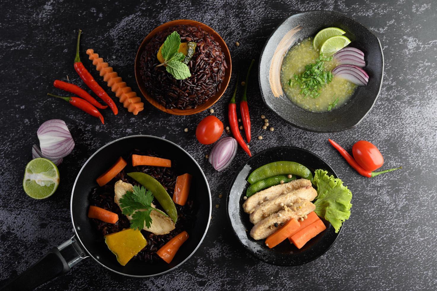 Assortiment de plats de légumes, de viande et de poisson sur un fond de pierre noire photo